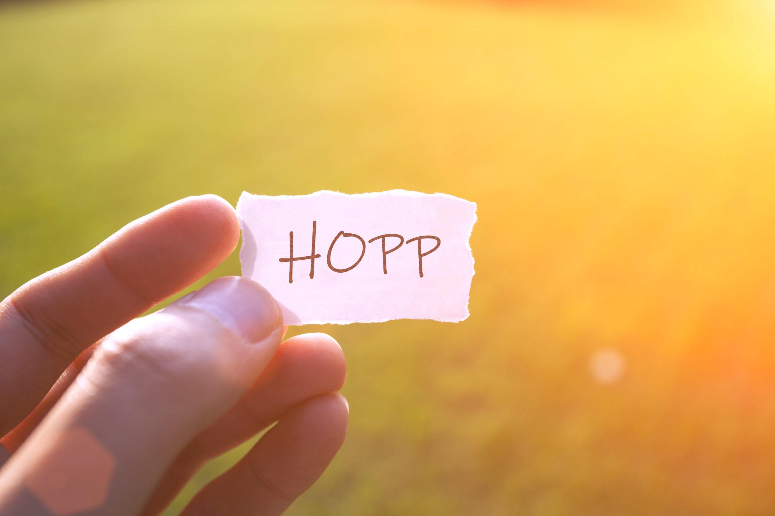 """en hand håller en lapp """"hopp"""""""